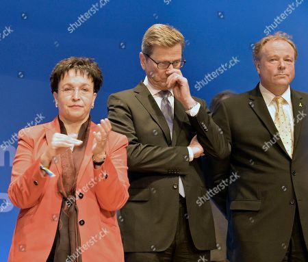 German Foreign Minister Guido Westerwelle, board member of the Free Democratic party FDP, center, reacts beside Federal Minister of Economic Cooperation and Development Dirk Niebel, right, and board member Birgit Homburger, left, stand on the podium at the Free Democratic party (FDP) election event in Berlin, after the first exit polls have been published