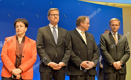 Board member of the Free Democratic party (FDP), Birgit Homburger, German Foreign Minister Guido Westerwelle, Federal Minister of Economic Cooperation and Development Dirk Niebel, and Christian Lindner, from left, stand on the podium at the FDP election event in Berlin, after the first exit polls have been published