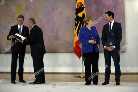 German Chancellor Angela Merkel, second right, talks to German Economy Minister Philipp Roesler, right, as German President Joachim Gauck, second left, hands over the dismissal documents to German Foreign Minister Guido Westerwelle, left, and all other federal ministers at the Bellevue palace in Berlin, Germany, . The ministers will stay in charge as an acting government until German Christian Democrats' and German Social Democrat 's planned coalition has formed a new government