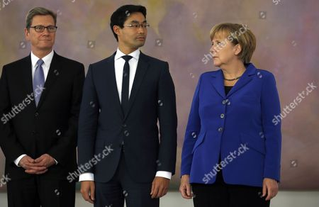 German Chancellor Angela Merkel, right, German Economy Minister Philipp Roesler, center, and German Foreign Minister Guido Westerwelle, left, attend a ceremony to receive the dismissal documents at the Bellevue Palace in Berlin, . The ministers will stay in charge as an acting government until German Christian Democrats' and German Social Democrats' planned coalition has formed a new government