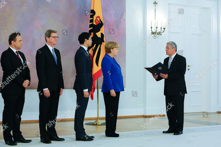 German President Joachim Gauck, right, hands over the dismissal documents to Chancellor Angela Merkel, Vice Chancellor and Economic Minister Philipp Roesler, Foreign Minister Guido Westerwelle and Interior Minister Hans-Peter Friedrich, from right, at Bellevue Palace in Berlin, . Following the Sept. 22, national election Angela Merkel will stay managing Chancellor until the planned coalition of Christian Democrats and Social Democrats has formed a new government