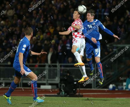 Croatia's Ivan Perisic jumps for the ball with Iceland's Olafur Ingi Skulason, right, during their World Cup qualifying playoff first leg soccer match in Reykjavik, Iceland