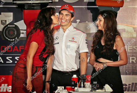 Sergio Perez Bollywood actress Neha Dhupia, left, kisses the cheek of McLaren Formula One driver Sergio Perez of Mexico as Aditi Rao Hydari stands beside him during a promotional event, in New Delhi, India, . Perez is in the country for the third edition of the Indian Grand Prix which will be held on Oct. 27