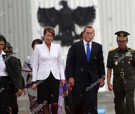 """Tony Abbott Australian Prime Minister Tony Abbott, center, and his wife Margie Abbott, left, walk, with Indonesia's coat of arms """"Garuda Pancasila"""", seen in background, after a wreath laying ceremony at Kalibata war heroes' cemetery in Jakarta, Indonesia, Monday, Sept. 30. 2013"""