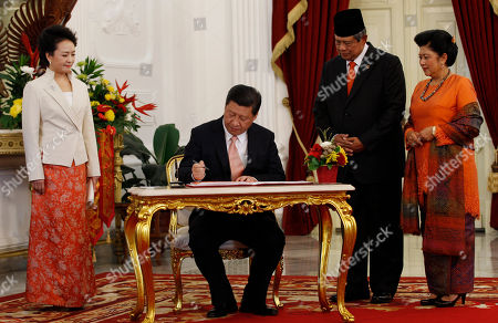 Susilo Bambang Yudhoyono, Xi Jinping Chinese President Xi Jinping signs a guest book as his wife Peng Liyuan, left, Indonesian President Susilo Bambang Yudhoyono, second from right, and his wife Ani Bambang Yudhoyono watch him before a meeting at Merdeka Palace in Jakarta, Indonesia,. Xi arrived here on Wednesday for his first visit to Southeast Asia since taking office, striving to boost ties and economic partnerships with the region's biggest country
