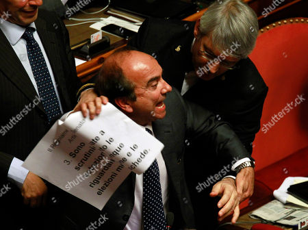 """Senator Domenico Scilipoti shows a paper during votation on whether to kick Italian Former Premier Silvio Berlusconi out of the Parliament because of his tax fraud conviction, in Rome The Italian Senate has expelled three-time ex-Premier Silvio Berlusconi from Parliament over his tax fraud conviction. The vote on Wednesday halts the 77-year-old Berlusconi's legislative run for at least six years, but does not mark the end of his political career. Berlusconi maintained his defiance ahead of the vote, declaring Wednesday a """"day of mourning for democracy"""" before thousands of cheering, flag-waving supporters outside his Roman palazzo"""