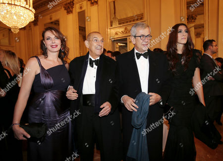 """Franco Tato', second from left, his wife Sonia Raule, and Chicco Testa, second from right, arrive at the Milan La Scala theater, Italy, for the season's opera opening. Milan opera house La Scala is concluding its bicentennial celebrations of Giuseppe Verdi's birth with Daniele Gatti conducting """"La Traviata"""" at the gala season opener Saturday. Although """"La Traviata"""" is Verdi's most popular opera, it hasn't been performed at La Scala, which was long Verdi's musical home, in more than a decade"""