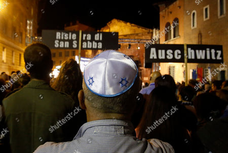 A participant wearing a Jewish kippah on his head attends a march marking the 70th anniversary of the roundup and deportation of Rome's Jews to concentration camps, in Rome's ghetto neighborhood, . Rome's Jewish community gathered Wednesday to commemorate the deportation amid deep anger over the late Nazi war criminal Erich Priebke and his Holocaust-denying final statement. Priebke died Friday in Rome, where he was serving a life term for his role in the 1944 massacre of 335 civilians at the Ardeatine Caves outside the capital. It was one of the worst atrocities of Germany's World War II occupation of Italy. His death at age 100 has unleashed a torrent of emotion, because he left behind a document in which he not only defended his actions but denied that Jews were gassed in Nazi death camps