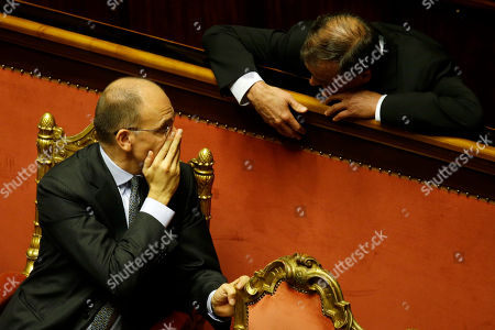 Italian Premier Enrico Letta, left, covers his mouth as he talks with Northern League party senator Roberto Calderoli at the Senate, in Rome, . Letta was putting his government's survival to confidence votes in Parliament on Wednesday amid a divisive split in Silvio Berlusconi's party that could at least temporarily save his fragile ruling coalition