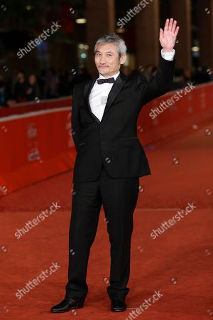 Director Tsui Hark waves whilst posing for photographers as arrives for the screening of his movie 'Di Renjie Shendu Longwang' (Young Detective Dee: Rise of the Sea Dragon) at the 8th edition of the Rome International Film Festival in Rome
