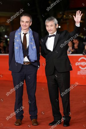 Director Tsui Hark, right, flanked by director Olivier Assayas poses for photographers as he arrives for the screening of his movie 'Di Renjie Shendu Longwang' (Young Detective Dee: Rise of the Sea Dragon) at the 8th edition of the Rome International Film Festival in Rome