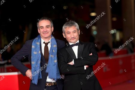 Director Tsui Hark, right, flanked by director Olivier Assayas poses during the Red carpet for the movie 'Di Renjie Shendu Longwang' (Young Detective Dee: Rise of the Sea Dragon) at the 8th edition of the Rome International Film Festival in Rome