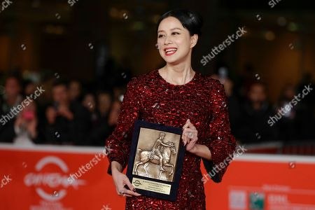 Actress Ni Hongjie, holding the special Marc'Aurelio Jury Award for the movie 'Blue Sky Bones', directed by Cui Jian, poses for photographers at the 8th edition of the Rome International Film Festival in Rome, . Director Cui Jian was awarded Saturday the special Marc'Aurelio Jury Award for the movie 'Blue Sky Bones