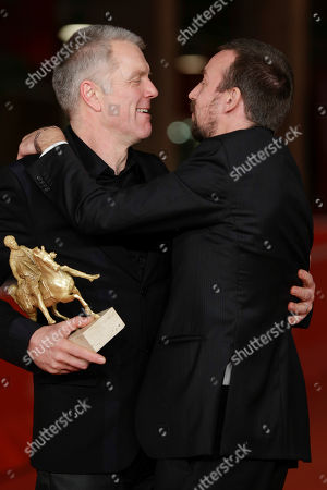 Stock Picture of Director Alberto Fasulo, right, and actor Branko Zavrsan, holding the Golden Marc'Aurelio Award for Best Film 'Tir', embrace as they pose for photographers at the 8th edition of the Rome International Film Festival, in Rome