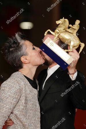 Director Alberto Fasulo, right, kisses his wife producer Nadia Trevisan, whilst holding the Golden Marc'Aurelio Award for Best movie 'Tir', as they pose for photographers at the 8th edition of the Rome International Film Festival, in Rome