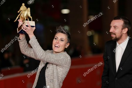 Producer Nadia Trevisan, left, holding the Golden Marc'Aurelio Award for Best movie 'Tir', and her husband director Alberto Fasulo pose for photographers at the 8th edition of the Rome International Film Festival, in Rome