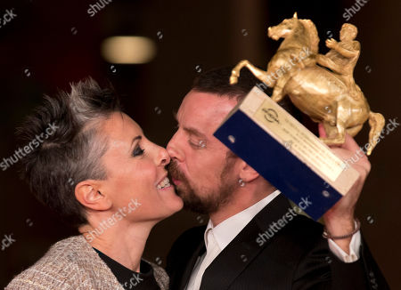 Director Alberto Fasulo, right, kisses his wife and producer Nadia Trevisan as he holds the Golden Marc'Aurelio Award for Best Film 'Tir' as he poses for photographers at the 8th edition of the Rome International Film Festival, in Rome