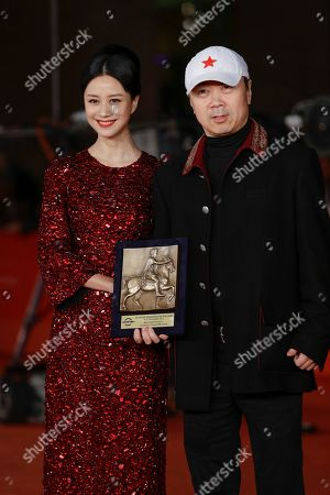 Director Cui Jian, right, flanked by actress Ni Hongjie, holding the special Marc'Aurelio Jury Award for the movie 'Blue Sky Bones', pose for photographers at the 8th edition of the Rome International Film Festival in Rome