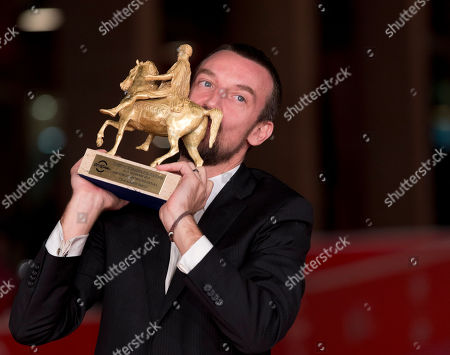 Director Alberto Fasulo kisses the Golden Marc'Aurelio Award for Best Film 'Tir' as he poses for photographers at the 8th edition of the Rome International Film Festival, in Rome
