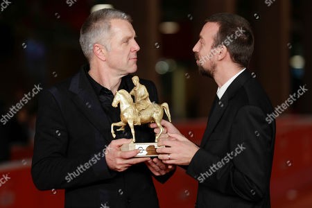 Director Alberto Fasulo, right, and actor Branko Zavrsan hold the Golden Marc'Aurelio Award for Best Film 'Tir' as they pose for photographers at the 8th edition of the Rome International Film Festival, in Rome