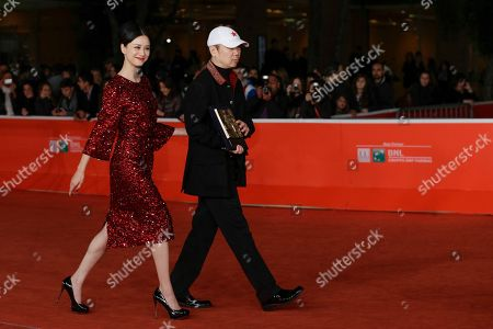 Director Cui Jian, right, holding the special Marc'Aurelio Jury Award for the movie 'Blue Sky Bones', and actress Ni Hongjie, arrive to poses for photographers at the 8th edition of the Rome International Film Festival in Rome