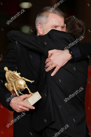 Director Alberto Fasulo, right, and actor Branko Zavrsan, holding the Golden Marc'Aurelio Award for Best Film 'Tir', embrace as they pose for photographers at the 8th edition of the Rome International Film Festival, in Rome