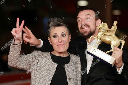 Director Alberto Fasulo, right, holding the Golden Marc'Aurelio Award for Best movie 'Tir', and his wife producer Nadia Trevisan pose for photographers at the 8th edition of the Rome International Film Festival, in Rome