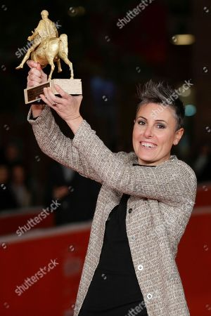 Producer Nadia Trevisan holds the Golden Marc'Aurelio Award for Best movie 'Tir', directed by her husband Alberto Fasulo, poses for photographers at the 8th edition of the Rome International Film Festival, in Rome