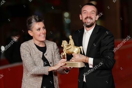 Director Alberto Fasulo, right, and his wife producer Nadia Trevisan hold the Golden Marc'Aurelio Award for Best movie 'Tir' as they pose for photographers at the 8th edition of the Rome International Film Festival, in Rome