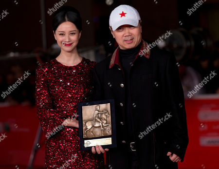 Director Cui Jian, right, flanked by actress Ni Hongjie, holds the special Marc'Aurelio Jury Award for he movie 'Blue Sky Bones' at the 8th edition of the Rome International Film Festival in Rome