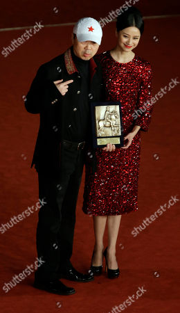 Director Cui Jian, left, and actress Ni Hongjie pose for photographers with the Special Mention award for the movie 'Lanse gutou' (Blue Sky Bones) at the 8th edition of the Rome International Film Festival, in Rome