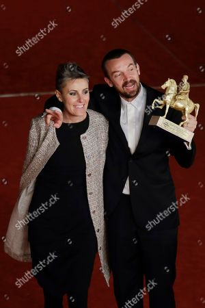 Director Alberto Fasulo, right, and his wife and producer Nadia Trevisan hold the Golden Marc'Aurelio Award for Best Film 'Tir' as they pose for photographers at the 8th edition of the Rome International Film Festival, in Rome