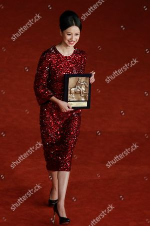 Actress Ni Hongjie, holding director Cui Jian's special Marc'Aurelio Jury Award for he movie 'Blue Sky Bones' poses for photographers at the 8th edition of the Rome International Film Festival in Rome