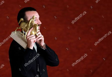 Director Alberto Fasulo holds the Golden Marc'Aurelio Award for Best Movie ' Tir ' as he poses for photographers at the 8th edition of the Rome International Film Festival, in Rome