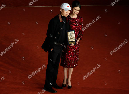 Director Cui Jian, left, flanked by actress Ni Hongjie, holds the special Marc'Aurelio Jury Award for he movie 'Blue Sky Bones' at the 8th edition of the Rome International Film Festival in Rome