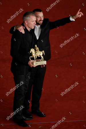 Stock Image of Director Alberto Fasulo, right, and actor Branko Zavrsan pose for photographers with the Golden Marc'Aurelio Award for Best Movie ' Tir ' at the 8th edition of the Rome International Film Festival, in Rome