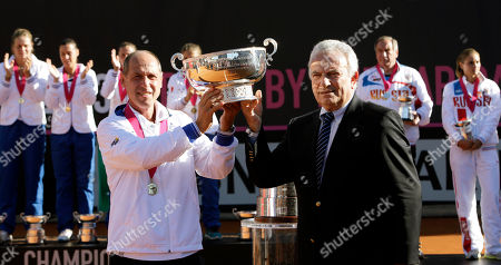 Italy coach Corrado Barazzutti, left, receives the trophy from Italian Tennis Federation President Francesco Ricci Bitti after winning the Fed Cup tennis final match against Russia, in Cagliari, Italy, . Italy won a fourth Fed Cup title with a whitewash 4-0 victory over Russia on Sunday as seventh-ranked Sara Errani cruised past Alisa Kleybanova before Flavia Pennetta and Karin Knapp won the dead doubles rubber