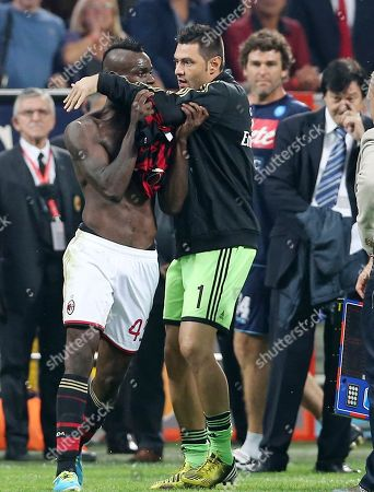 """AC Milan forward Mario Balotelli, left, is restrained by teammate Marco Amelia after receiving a red card at the end of the Serie A soccer match between AC Milan and Napoli at the San Siro stadium in Milan, Italy. Mario Balotelli has been banned for three matches following a confrontation with the referee after AC Milan's loss to Napoli. Balotelli, who missed a penalty and scored in Sunday's match, was shown a second yellow card after the final whistle for his protests. The Italy striker will miss the next three matches for making """"insulting and intimidating comments"""" towards the referee"""