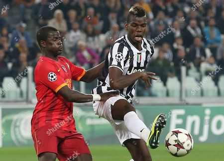 Juventus midfielder Paul Pogba, right, of France, challenges for the ball with Galatasaray defender Emmanuel Eboue, of Ivory Coast, during a Champions League, Group B, soccer match at the Juventus stadium in Turin, Italy