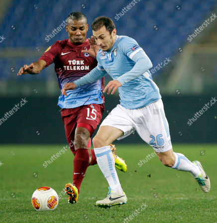 Trabzonspor midfielder Florent Malouda, left, and Lazio defender Stefan Radu, of Romania, fight for the ball during an Europa League Group J soccer match, at Rome's Olympic stadium