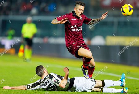 Udinese's Thomas Heurtaux, of France, on the ground, slides in to tackle Livorno's Leandro Greco during a Serie A soccer match between Livorno and Udinese, in Leghorn, Italy