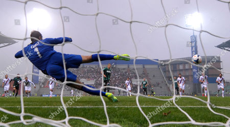 Sassuolo's Domenico Berardi, center, scores on a penalty past Bologna goalkeeper Gianluca Curci, left, during their Serie A soccer match at Reggio Emilia's Mapei stadium, Italy