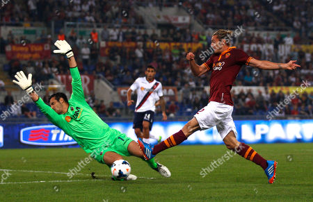 AS Roma's Federico Balzaretti, right, challenge for the ball with Bologna goalkeeper Gianluca Curci during a Serie A soccer match between AS Roma and Bologna at Rome's Olympic stadium