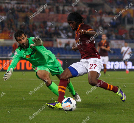 AS Roma's Gervinho of Ivory Coast challenge for the ball with Bologna goalkeeper Gianluca Curci during a Serie A soccer match between AS Roma and Bologna at Rome's Olympic stadium