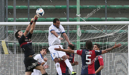 Cagliari goalkeeper Michael Agazzi, left, and Inter Milan's Rolando, jump for the ball during the Serie A soccer match between Cagliari and Inter, at the Nereo Rocco Stadium in Trieste, Italy