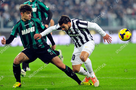 Juventus forward Carlos Tevez, of Argentina, challenges the ball with Sassuolo defender Luca Antei during a Serie A soccer match between Juventus and Sassuolo at the Juventus stadium, in Turin, Italy