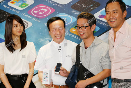 Stock Image of Hidenori Sato,Kaoru Kato,Maki Horikita,Ken Watanabe Hidenori Sato, 39, the first person to get newly released Apple's iPhone 5S, shows off as he poses for photos with NTT docomo President Kaoru Kato, second left, actress Maki Horikita and actor Ken Watanabe, right, during a ceremony to mark the first day sales of the latest iPhones 5C and 5S at a store in Tokyo on Friday morning