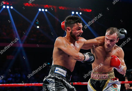 Evgeny Gradovich, Billy Dib Russia's Evgeny Gradovich, right, and Australia's Billy Dib exchange their punches at their IBF featherweight title bout, in Macau. Gradovich retained the title when Dib quit in the ninth round