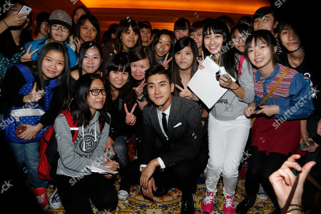 """Choi Si-won South Korean singer-actor Choi Si-won, center, poses with his fans for a photo after a promotional event for his latest movie """"Helios"""" in Macau"""