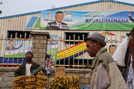 The election banners of Presidential candidate Dr. Robinson Jean Louis, rear, behind a man selling bananas at his makeshift stall in the city of Antananarivo, Madagascar, . Madagascar will hold elections on Friday that organizers hope will end political tensions that erupted in a 2009 coup and help lift the aid-dependent country out of poverty. The island nation in the Indian Ocean plunged into turmoil after Andry Rajoelina, the current president, forcibly took power from former President Marc Ravalomanana with the backing of the military